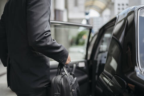 Mid-section of businessman getting into a taxi - JPIF00209