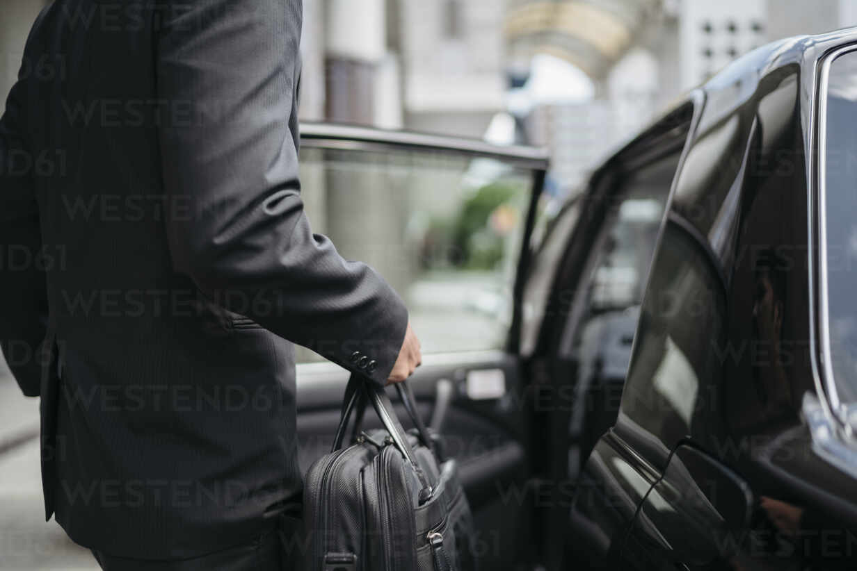 Mid-section of businessman getting into a taxi - JPIF00209 - Juri Pozzi/Westend61