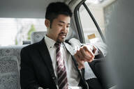 Young businessman in a taxi checking the time - JPIF00212