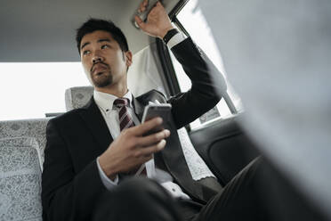 Young businessman with cell phone in a taxi - JPIF00215