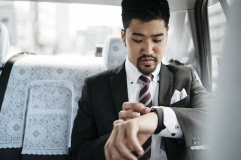 Young businessman in a taxi checking the time - JPIF00218