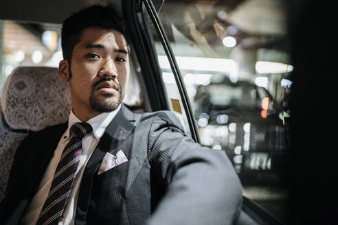 Portrait of confident young businessman in a taxi - JPIF00224