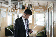 Young businessman using cell phone on a train - JPIF00230