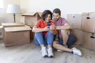 Happy couple using cell phone in new home - WPEF01923