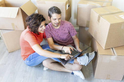 Happy couple moving into new home using laptop - WPEF01929