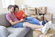 Happy couple using cell phone on couch in new home - WPEF01935