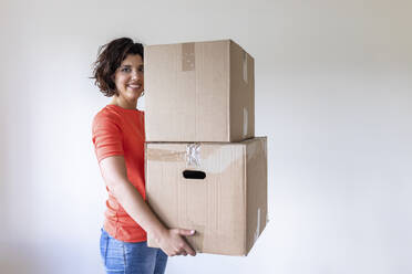 Woman moving into new home carrying cardboard boxes - WPEF01941