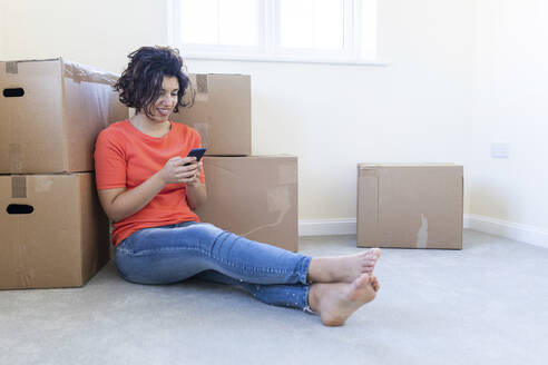Woman sitting on the floor in new home using cell phone - WPEF01950