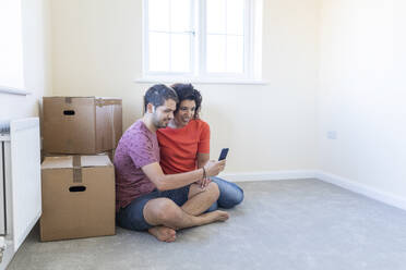 Happy couple sitting on the floor in new home using cell phone - WPEF01953