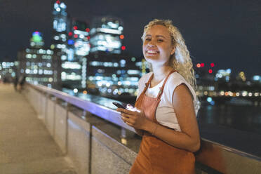Young woman in London at night using her smartphone - WPEF01986