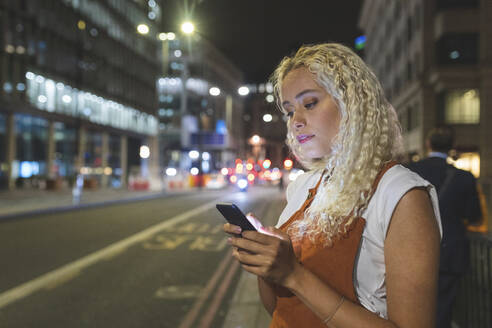 Young woman in London at night looking at her smartphone - WPEF01989