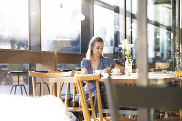 Woman using cell phone in a cafe - FKF03629