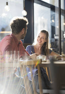 Smiling woman and man talking at table in a cafe - FKF03632
