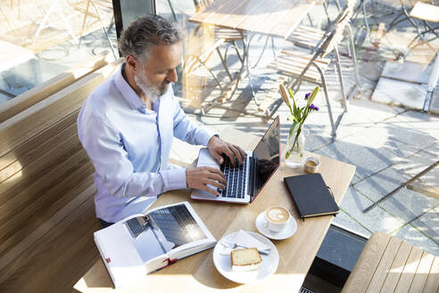 Mature man using laptop in a cafe with book on table - FKF03641
