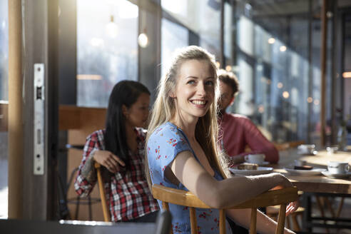 Portrait of smiling woman with friends in a cafe - FKF03644
