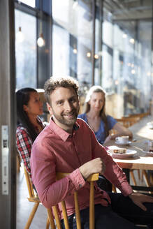 Portrait of smiling man with friends in a cafe - FKF03647