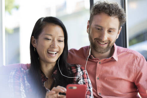 Happy man and woman with cell phone and earbuds in a cafe - FKF03653