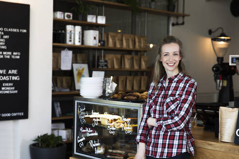 Portrait of smiling woman at the counter of a cafe - FKF03656