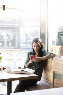 Woman with earbuds and cell phone in a cafe - FKF03659