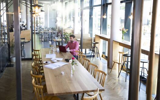 Young man using laptop at wooden table in a cafe - FKF03668