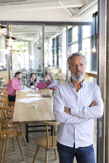 Portrait of mature businessman in a cafe with colleagues having a meeting in background - FKF03674