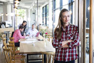 Portrait of casual businesswoman in a cafe with colleagues having a meeting in background - FKF03677