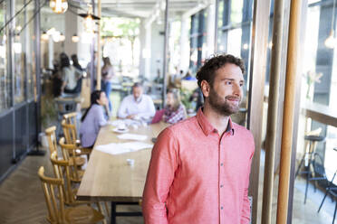 Portrait of casual businessman in a cafe with colleagues having a meeting in background - FKF03683