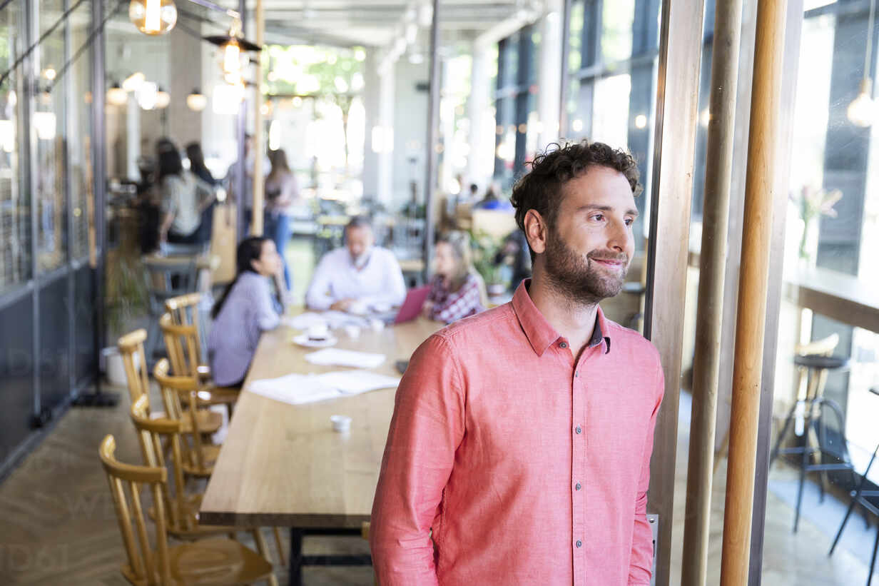 Portrait of casual businessman in a cafe with colleagues having a meeting in background - FKF03683 - Florian Küttler/Westend61