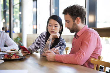 Casual business people having a meeting in a cafe using cell phone - FKF03689