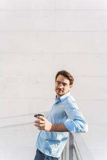 Portrait of casual businessman with takeaway coffee - AFVF03977