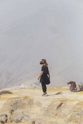 Young woman with espirator mask at Ijen volcano, Java, Indonesia - KNTF03584