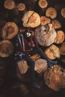 Portrait of young woman at stack of wood - DAMF00115