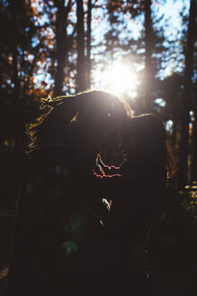 Silhouette of young couple in love in forest - DAMF00121