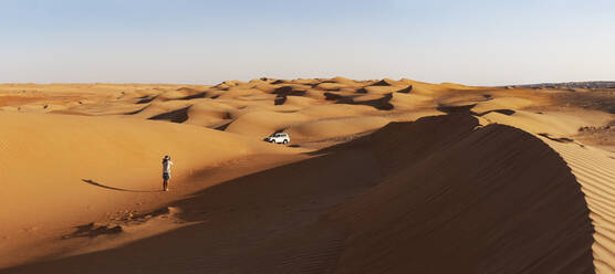 Man with off-road vehicle, taking pictures in the desert, Wahiba Sands, Oman - WWF05276
