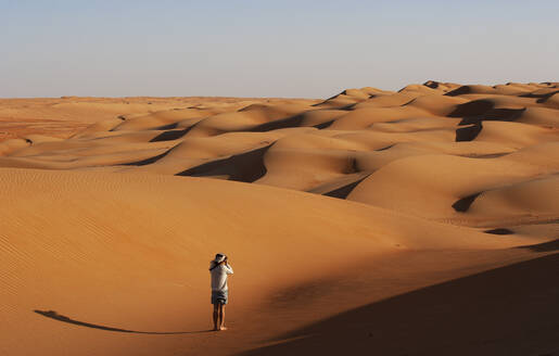 Man taking pictures in the desert, Wahiba Sands, Oman - WWF05279