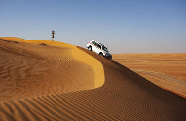 Man with off-road vehicle, taking pictures in the desert, Wahiba Sands, Oman - WWF05282