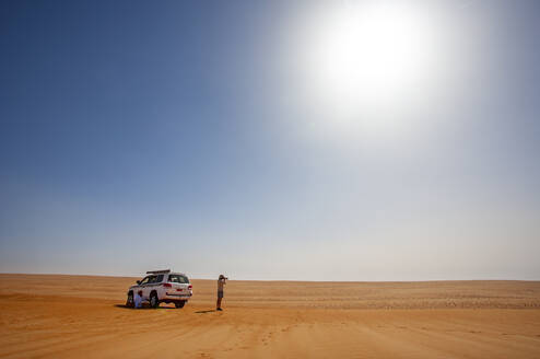 Man with off-road vehicle, taking pictures in the desert, Wahiba Sands, Oman - WWF05288