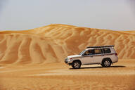 Tourist driving in desrt in off-road vehicle, Wahiba Sands, Oman - WWF05291