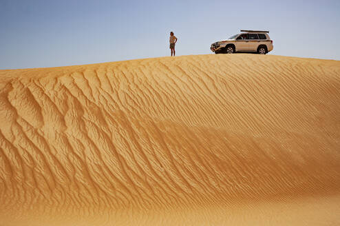 Man standing in the desert, next to off-road vehicle, Wahiba Sands, Oman - WWF05297