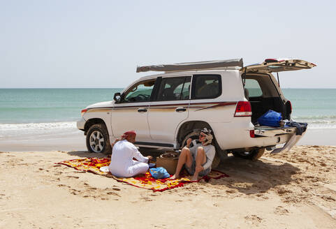 Tourist having a coffee break with his local driver at the Indian Ocean, Oman - WWF05306
