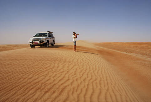 Man taking pictures in the desert, next to off-road vehicle,  Wahiba Sands, Oman - WWF05312
