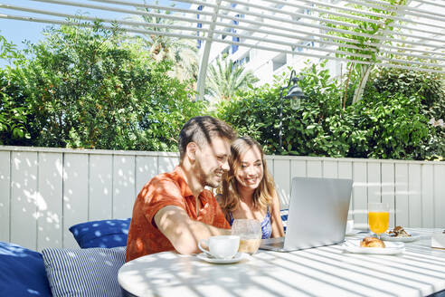 Cheerful young couple using laptop during breakfast - JNDF00113