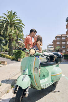 Young couple kissing at a vintage motor scooter - JNDF00116