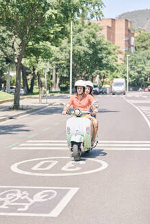 Young couple riding vintage motor scooter on urban road - JNDF00119