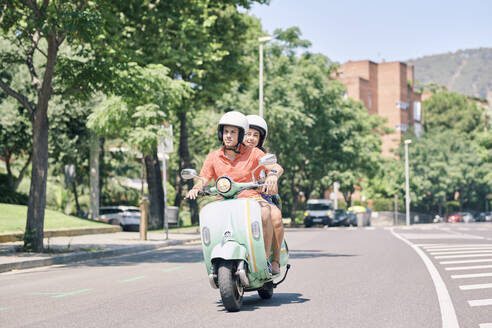Young couple riding vintage motor scooter on urban road - JNDF00122