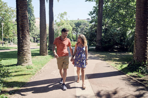 Smiling young couple walking hand in hand through a park - JNDF00125
