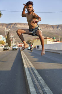 Tribal man with his traditional arch and arrows jumping on a median stripe, Lubango, Angola - VEGF00765