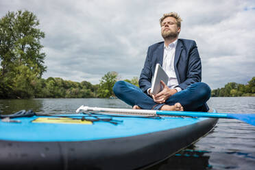 Businessman with laptop sitting on SUP board on a lake - JOSF03782