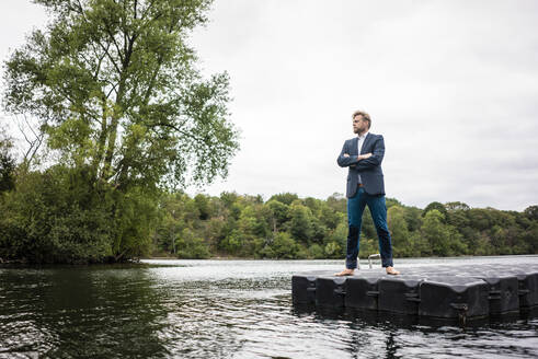 Businessman standing on a float a lake - JOSF03785