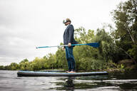 Businessman wearing VR glasses on SUP board on a lake - JOSF03794